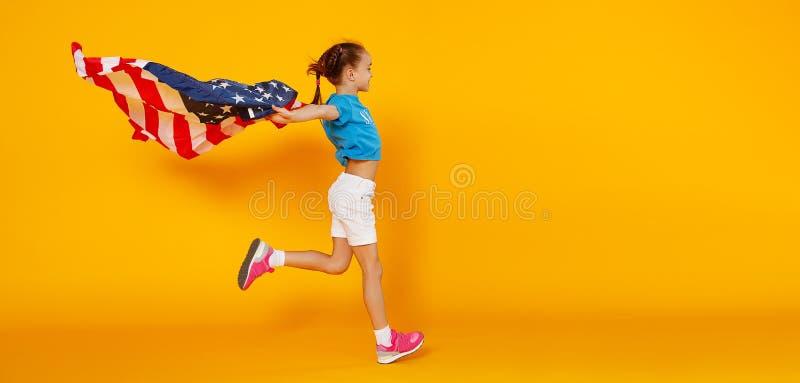 Ragazza felice del bambino con la bandiera degli Stati Uniti d'America U.S.A. su fondo giallo fotografie stock libere da diritti