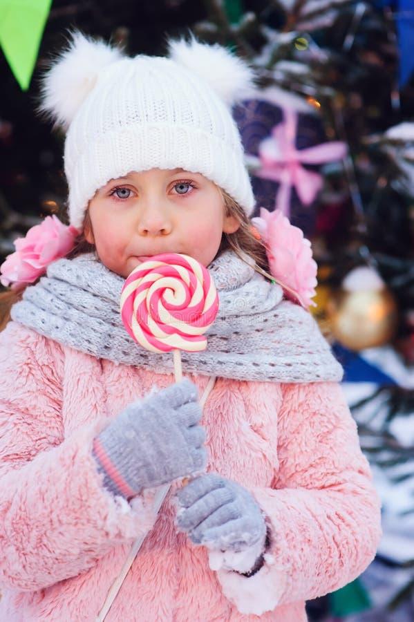 ragazza felice del bambino con la caramella di natale Ritratto di vacanza invernale all'albero di Natale immagine stock