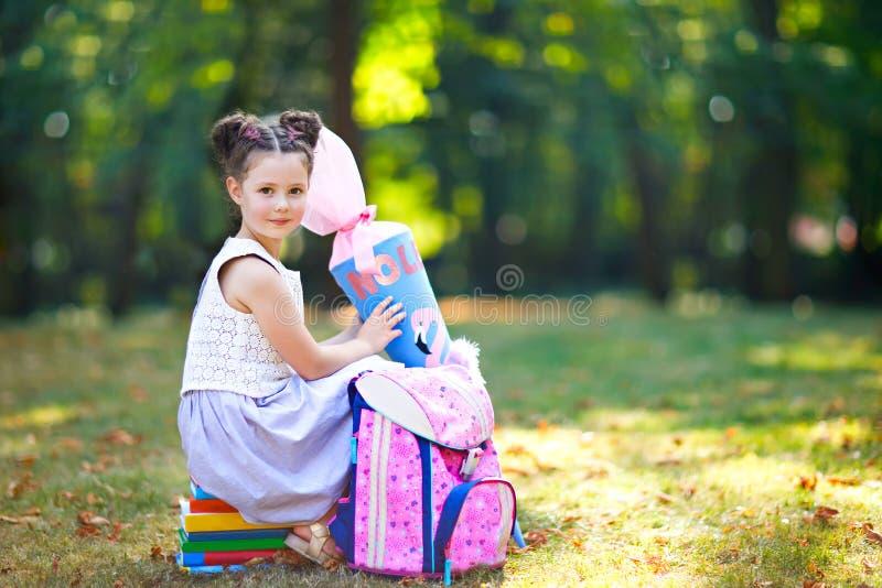 Ragazza felice del bambino con lo zaino o cartella, libri e grande borsa o cono di scuola tradizionali in Germania per la prima fotografie stock