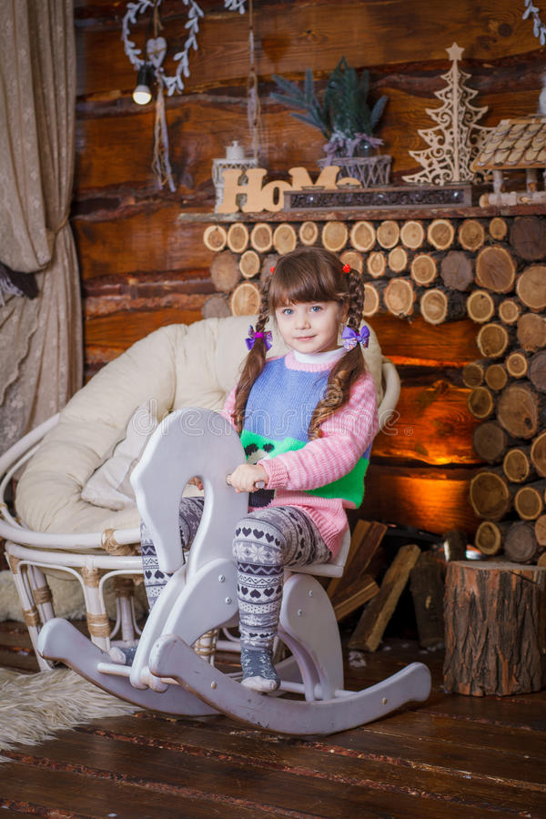 Ragazza felice del bambino divertendosi con il giocattolo di legno del cavallo fotografia stock libera da diritti
