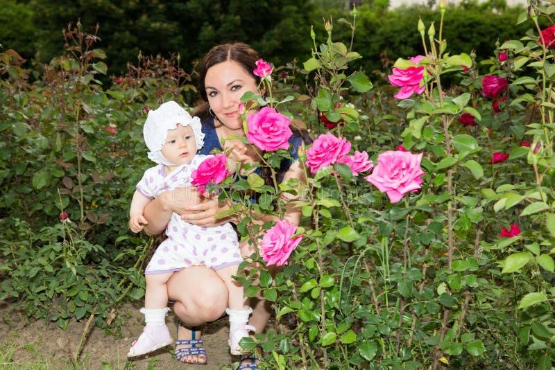 Ragazza felice del bambino e della mamma che abbraccia in fiori.  Bella madre ed il suo bambino all'aperto fotografia stock