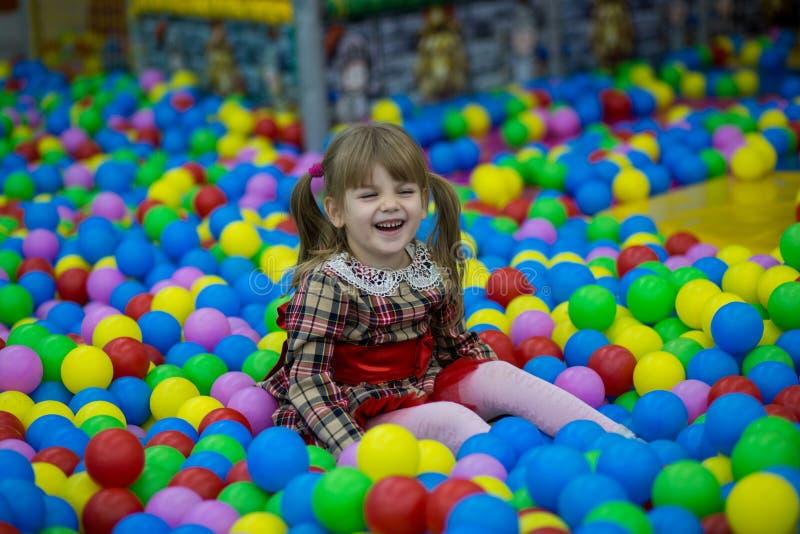 Ragazza felice del bambino nel gioco rosso del vestito in stagno con le palle di plastica variopinte immagini stock