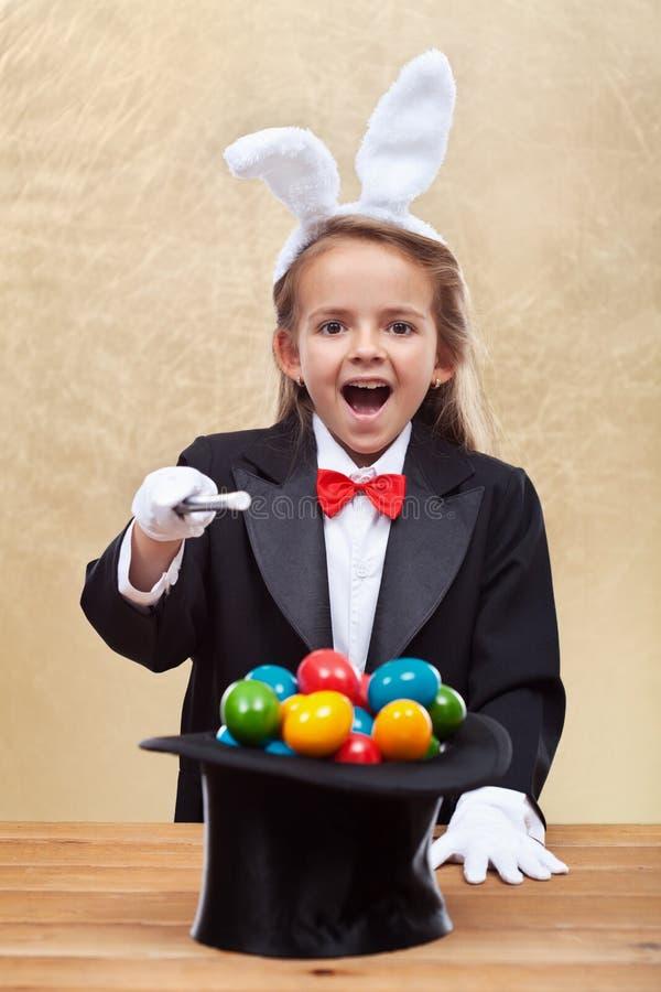 Ragazza felice del mago che evoca le uova di Pasqua variopinte immagini stock libere da diritti