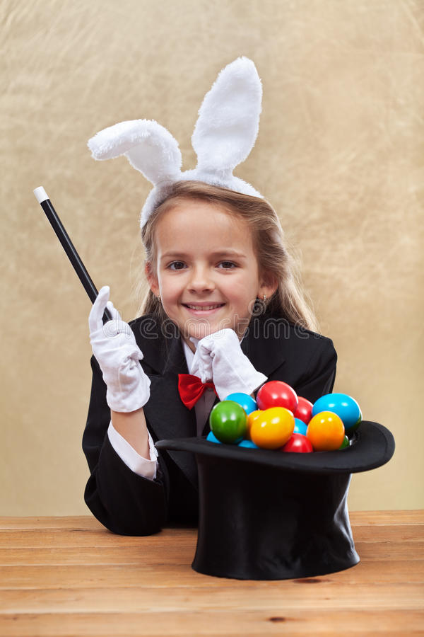 Ragazza felice del mago che produce le uova di Pasqua con i suoi poteri fotografia stock libera da diritti