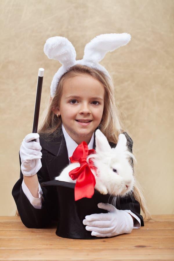 Ragazza felice del mago con il coniglietto bianco in un cappello fotografia stock libera da diritti