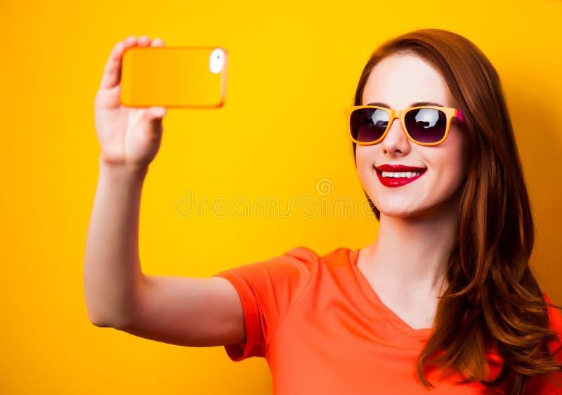 Ragazza felice della testarossa con il telefono cellulare su fondo giallo immagine stock libera da diritti