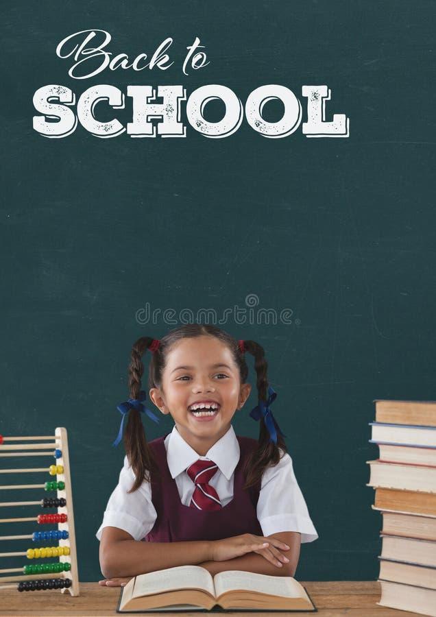Ragazza felice dello studente alla tavola contro la lavagna verde con di nuovo al testo di scuola fotografie stock