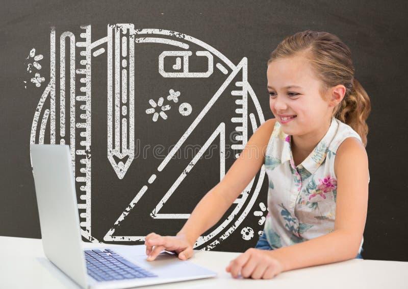 Ragazza felice dello studente alla tavola facendo uso di un computer contro la lavagna grigia con la scuola ed il grafico di istr immagini stock libere da diritti