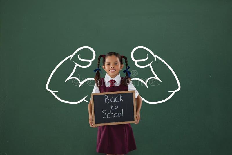 Ragazza felice dello studente con il grafico dei pugni che tiene una piccola lavagna contro la lavagna verde fotografia stock