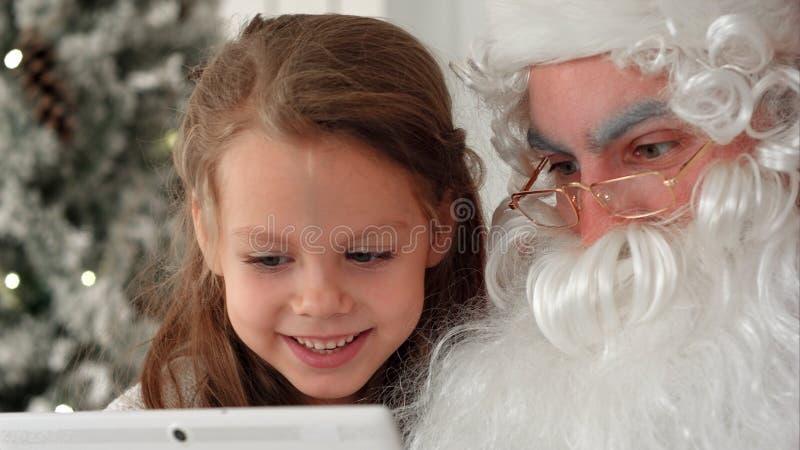 Ragazza felice e Santa Claus che esaminano i presente sul PC della compressa accanto all'albero di Natale fotografie stock libere da diritti