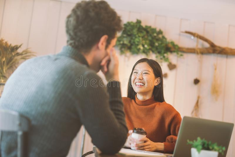 Ragazza felice ed amici asiatici che chiacchierano e che utilizzano computer portatile nel caffè al caffè della caffetteria in un immagini stock libere da diritti
