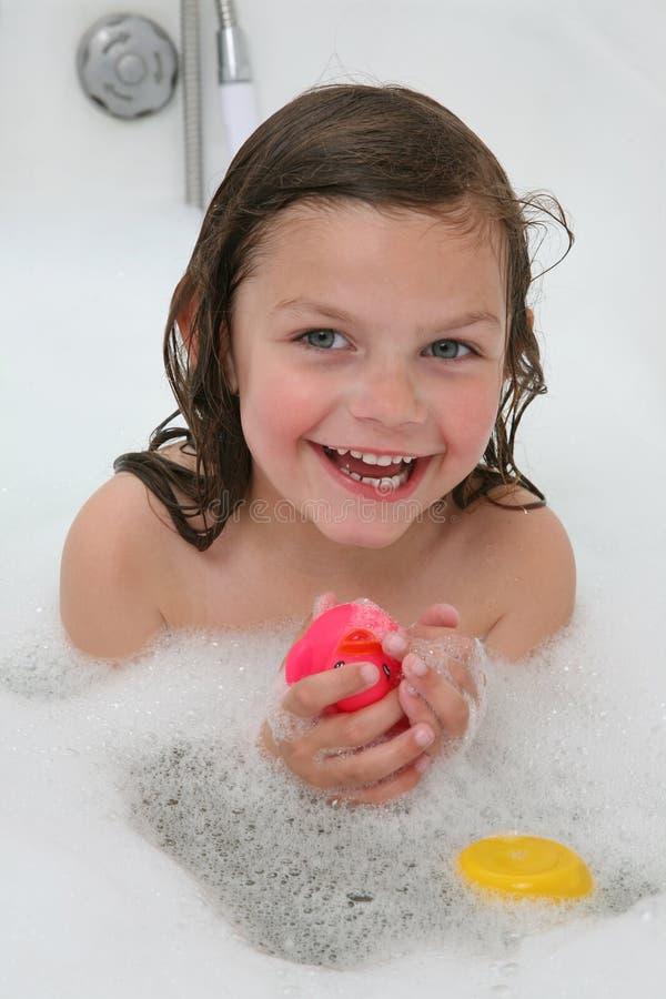 Ragazza felice nel bagno di bolla fotografia stock
