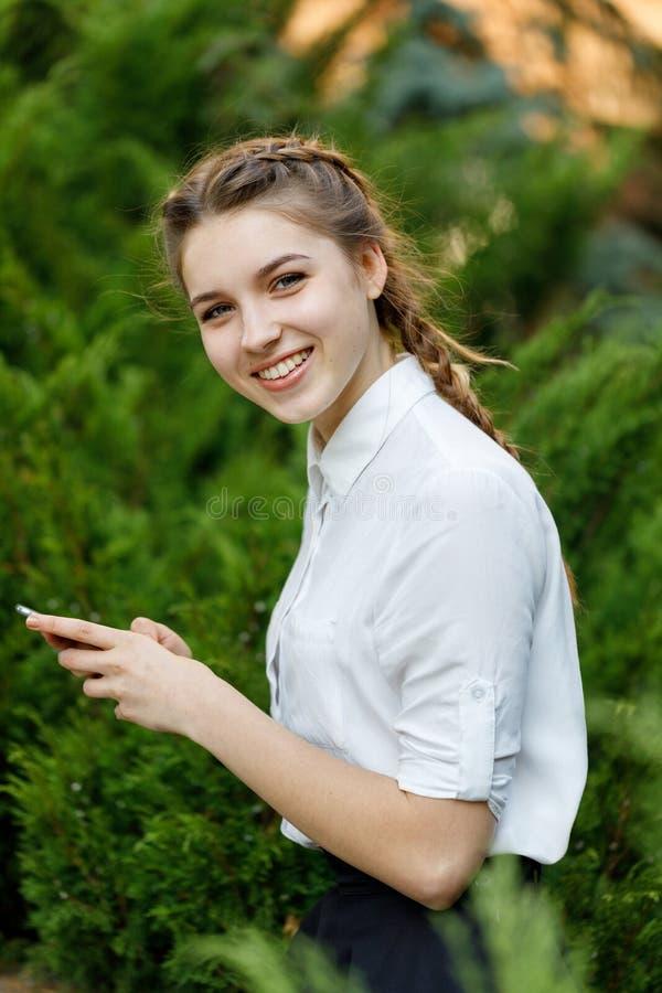 Ragazza felice in parco con il telefono in mani fotografia stock