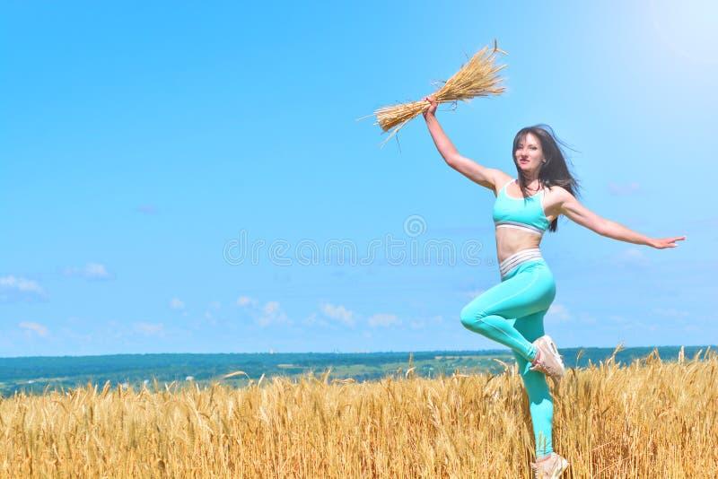 Ragazza felice sportiva che salta in un giacimento di grano fotografia stock libera da diritti