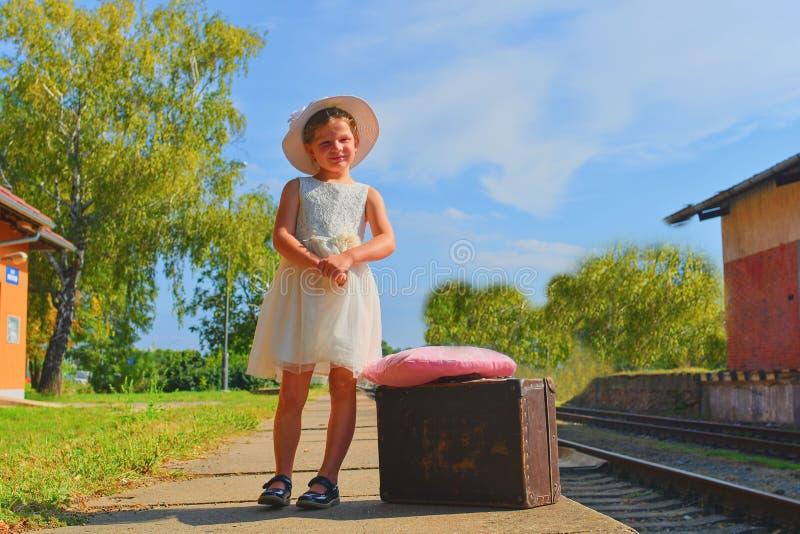 Ragazza felice su una stazione ferroviaria, aspettante il treno con la valigia d'annata Viaggio, festa e concetto di chilhood Ins immagini stock libere da diritti