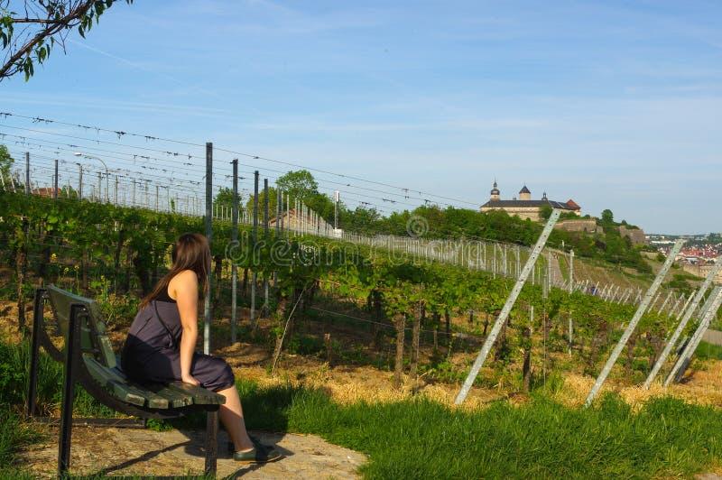 Ragazza felice sul banco che si rilassa in vista del landcape del giacimento dell'uva e del Festung o fortificazione Marienberg n fotografia stock