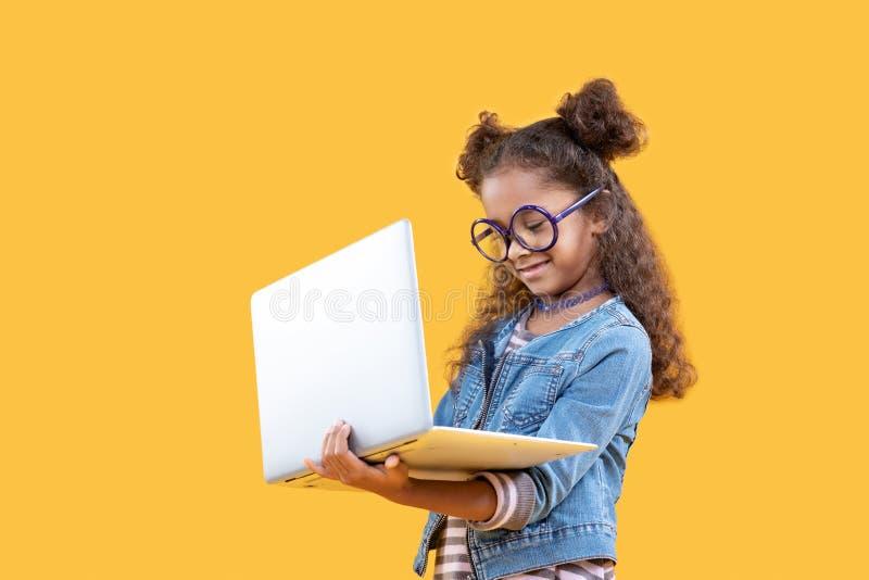 Ragazza felice sveglia che esamina lo schermo di computer fotografie stock libere da diritti