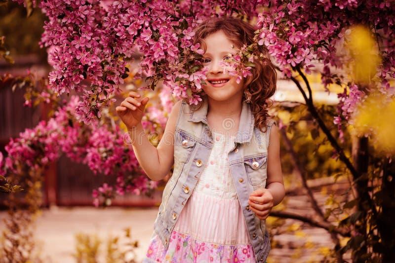 Ragazza felice sveglia del bambino che gioca e che si nasconde all'albero di fioritura del crabapple nel giardino di primavera fotografia stock libera da diritti