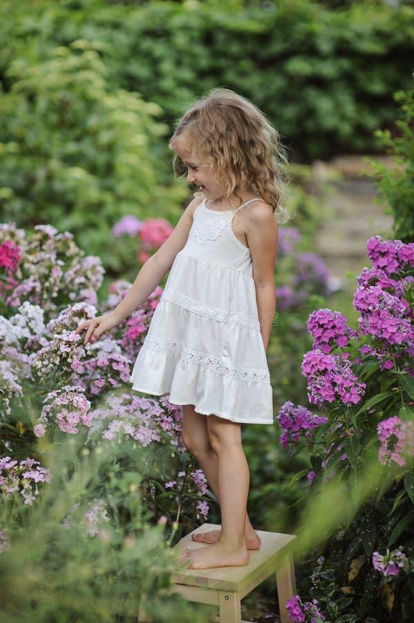 Ragazza felice sveglia del bambino che gioca nel giardino di fioritura di estate immagine stock libera da diritti