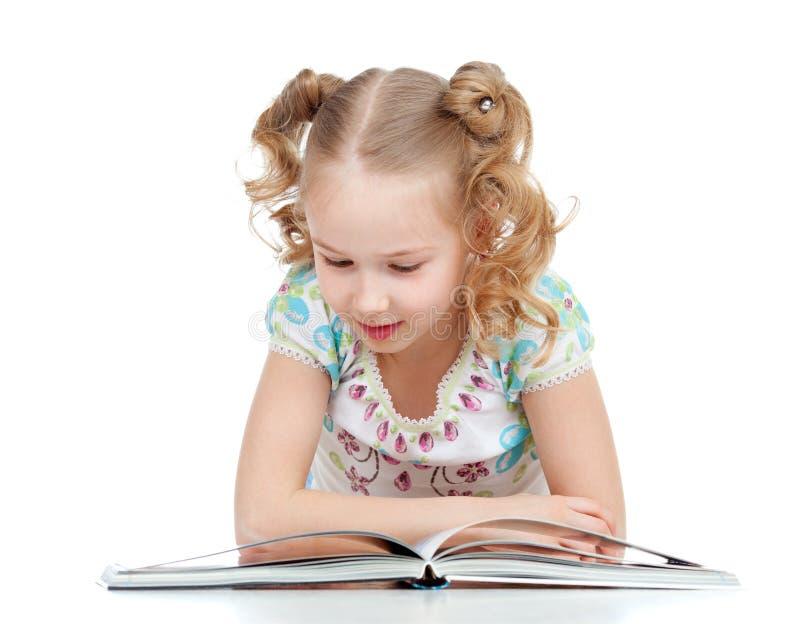 Ragazza felice sveglia del bambino che legge un libro immagini stock libere da diritti