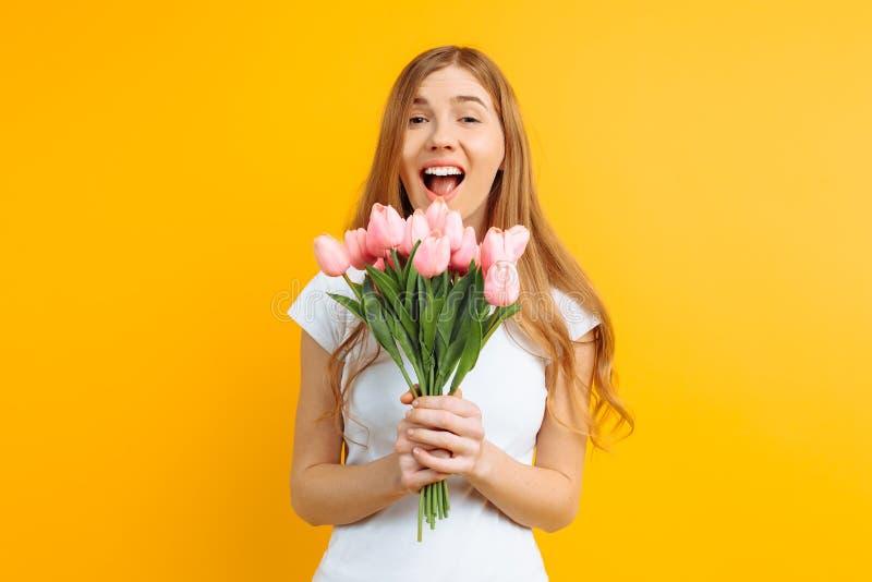 Ragazza felice, tenente un mazzo dei fiori in sua mano, contentissimo con il regalo su un fondo giallo fotografia stock libera da diritti