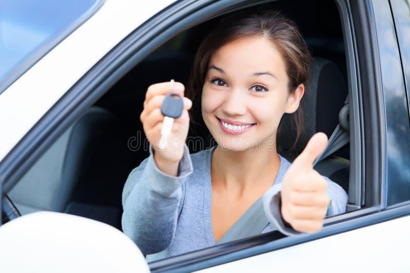 Ragazza felice in un'automobile che mostra un tasto immagini stock