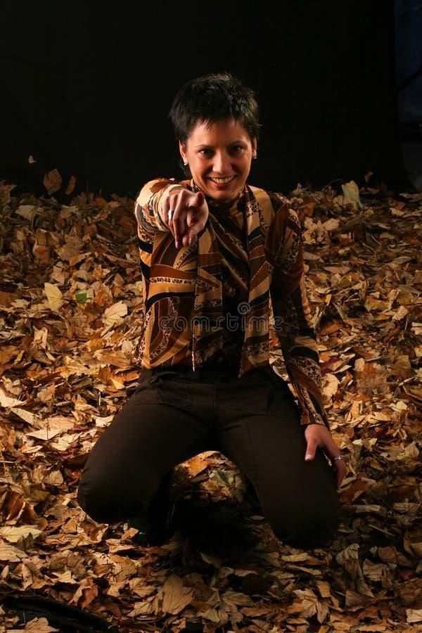 Ragazza in foglie di autunno fotografia stock