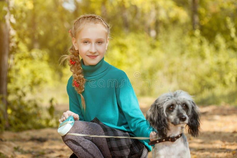Ragazza freckled sorridente sveglia che posa con il cane fotografia stock