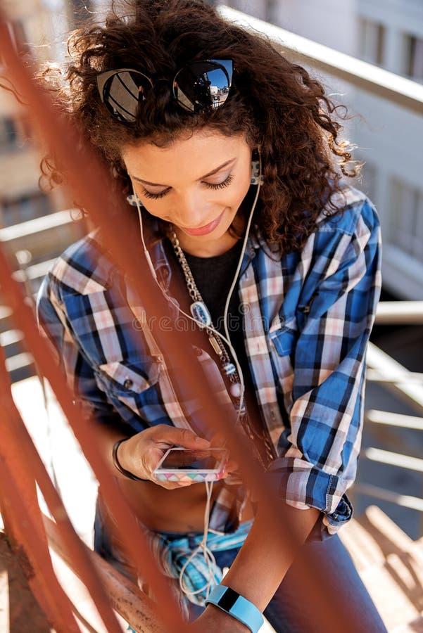 Ragazza fresca del mulatto che per mezzo dello smartphone sulla scala fotografie stock libere da diritti