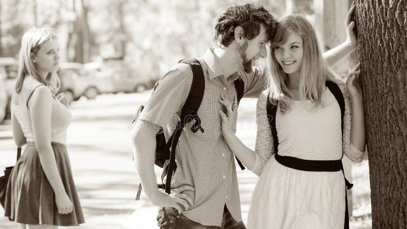 Ragazza gelosa che esamina le coppie di flirt all'aperto fotografie stock