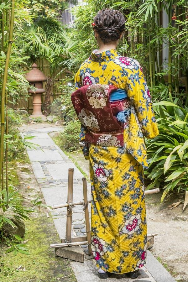 Ragazza giapponese in bello vestito tradizionale in un giardino di bambù, Kyoto, Giappone immagini stock libere da diritti