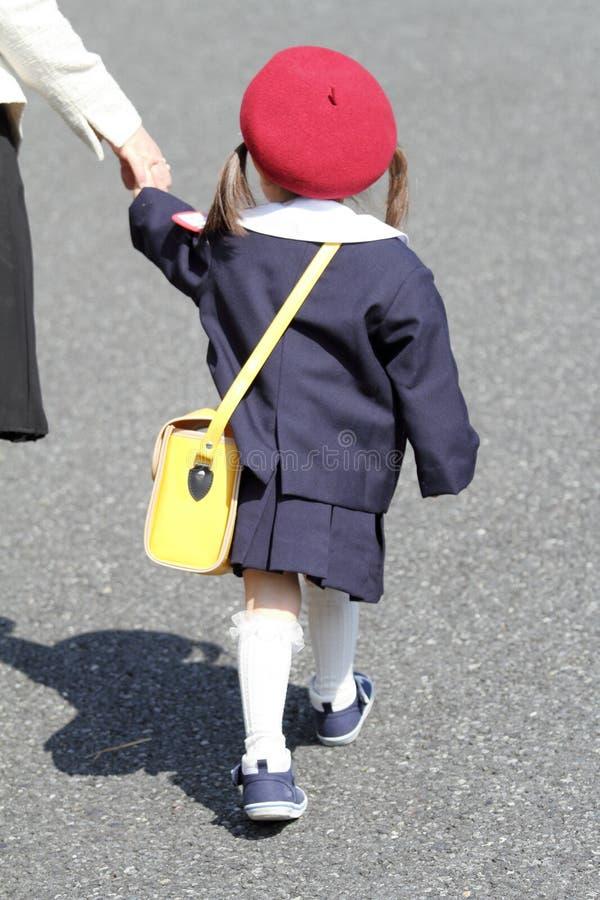 Ragazza giapponese in uniforme di asilo che afferra la sua figura di ritirata della mano del ` s della madre immagine stock libera da diritti