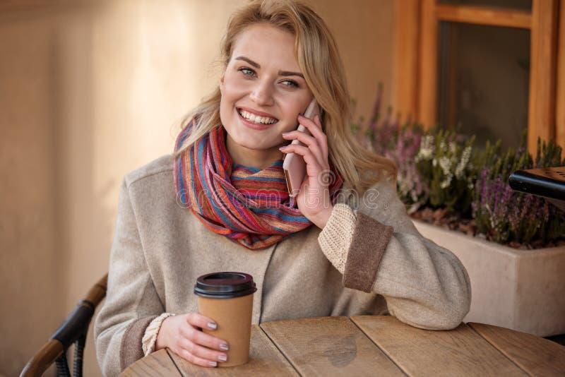 Ragazza giovanile che gode del caffè espresso caldo mentre parlando dal telefono cellulare fotografia stock libera da diritti