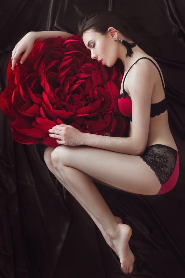 Ragazza graziosa in biancheria intima rosa con il grande fiore di carta fotografia stock