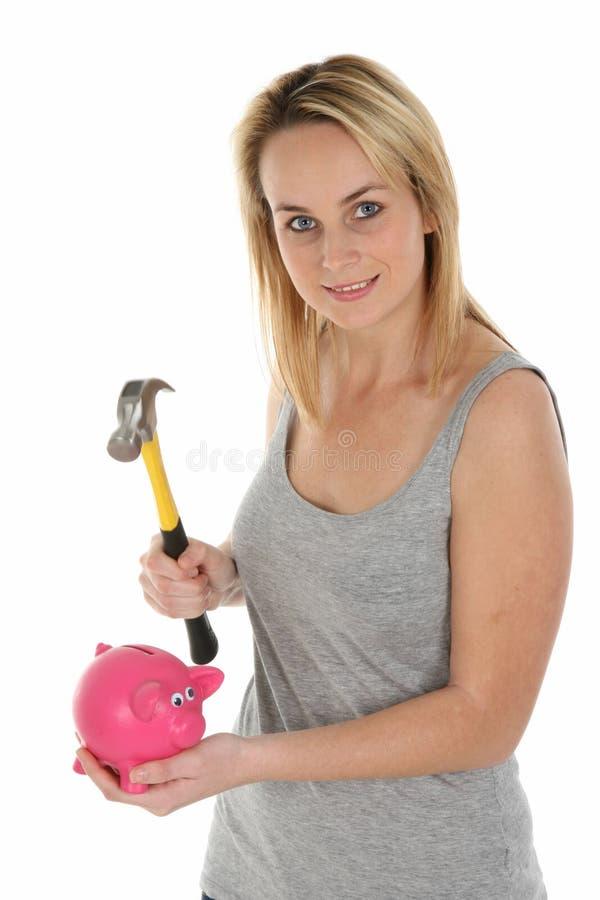 Ragazza graziosa che apre la Banca Piggy con il martello fotografie stock libere da diritti