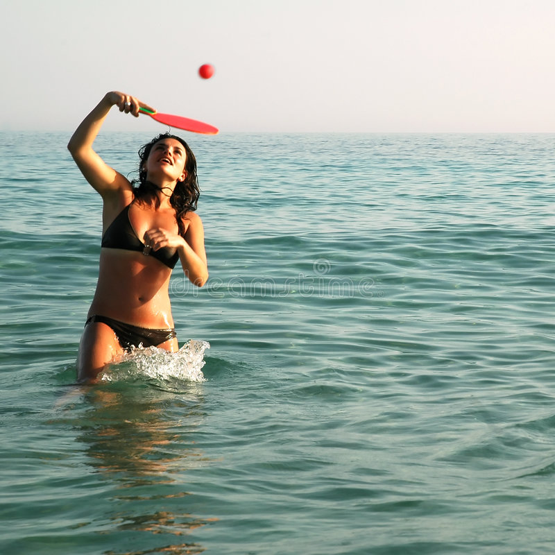 Ragazza graziosa che gioca sfera nell'oceano fotografie stock libere da diritti