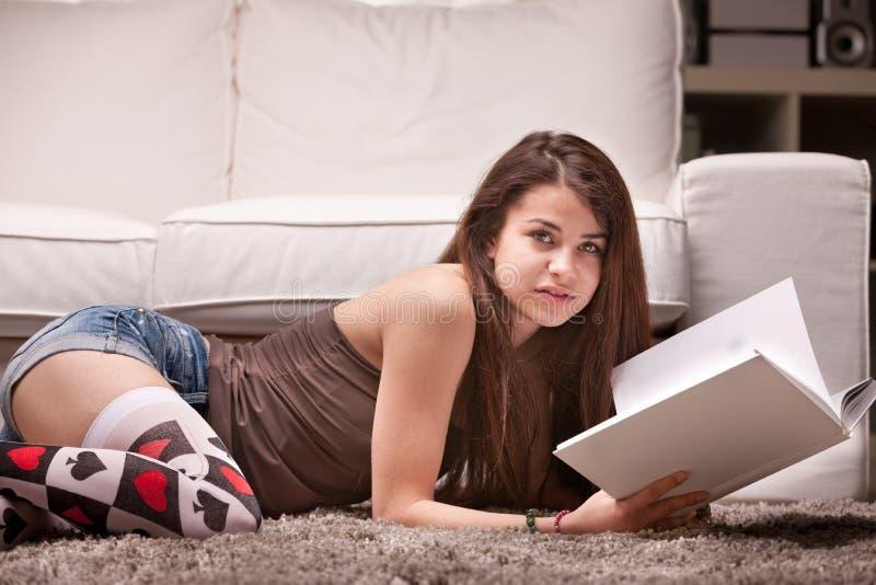 Ragazza graziosa che legge un libro sul tappeto immagine stock