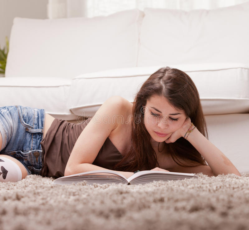 Ragazza graziosa che legge un libro sul tappeto immagine stock libera da diritti