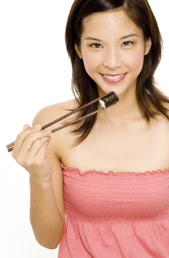 Ragazza graziosa che mangia alimento giapponese fotografie stock libere da diritti