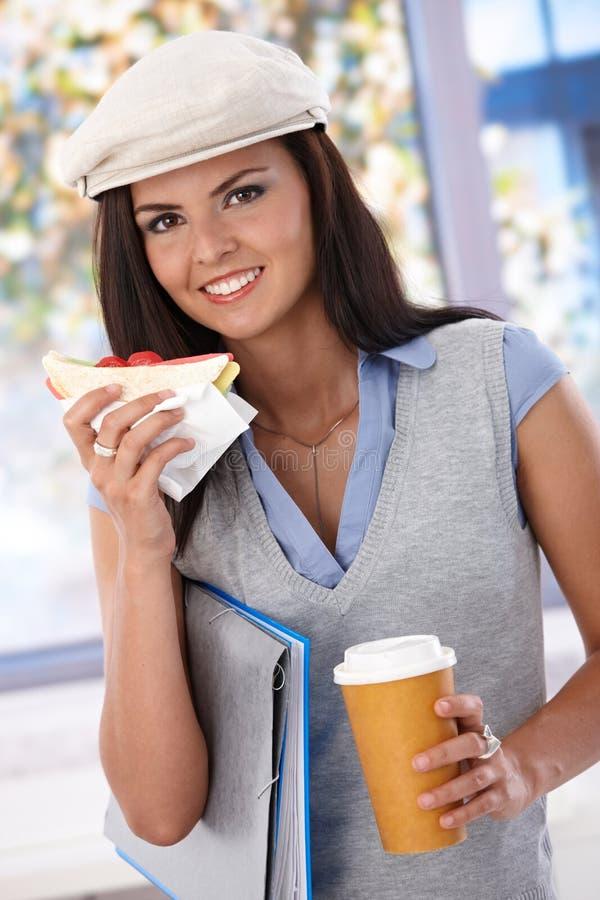 Ragazza graziosa che mangia il panino ed il caffè di randello immagine stock libera da diritti