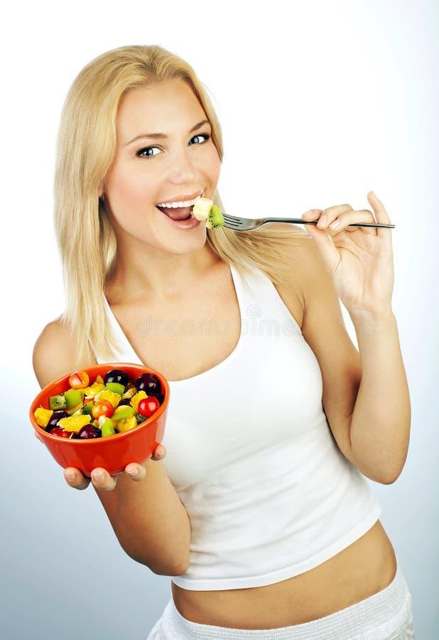 Ragazza graziosa che mangia la frutta fotografia stock libera da diritti