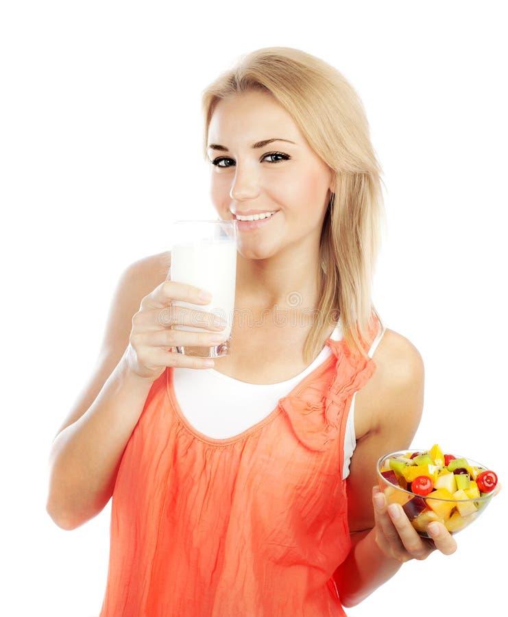 Ragazza graziosa che mangia la frutta e latte alimentare immagini stock