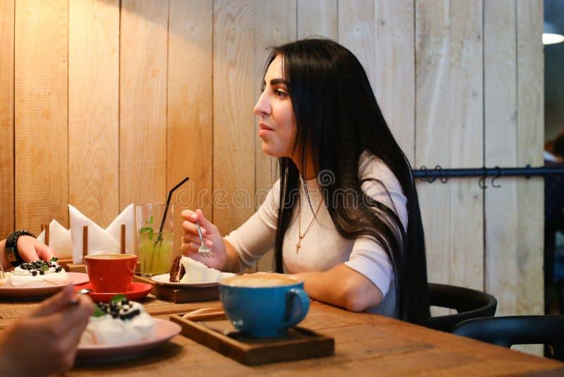 Ragazza graziosa che parla, ascoltante, mangiante e sorridente alla tavola in c fotografia stock