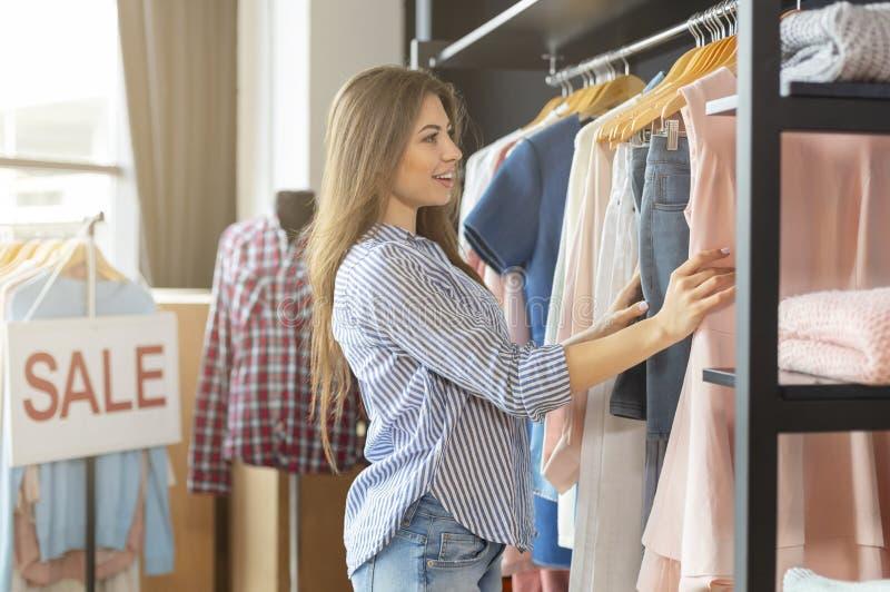 Ragazza graziosa che sceglie i vestiti al negozio, tempo di vendite fotografie stock libere da diritti
