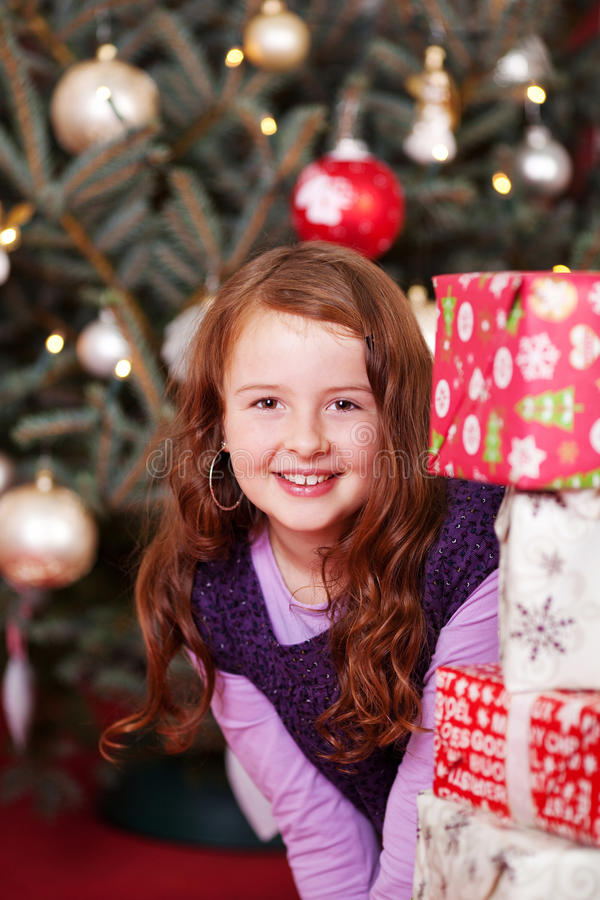 Ragazza graziosa che scruta intorno ai regali di Natale fotografia stock libera da diritti