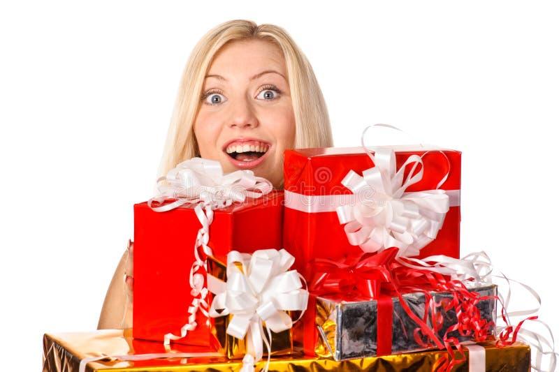 Ragazza graziosa che si nasconde dietro i regali di Natale immagini stock libere da diritti