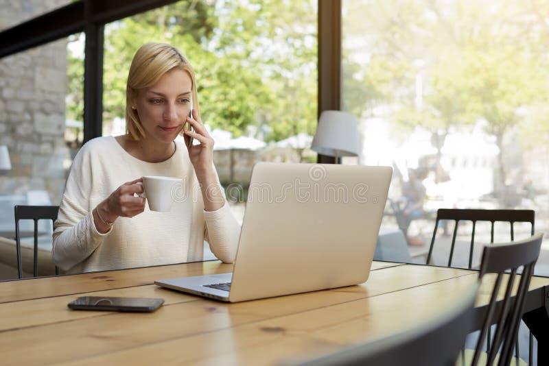 Ragazza graziosa che si siede nel caffè bevente del caffè accogliente luminoso e che parla sul telefono immagine stock