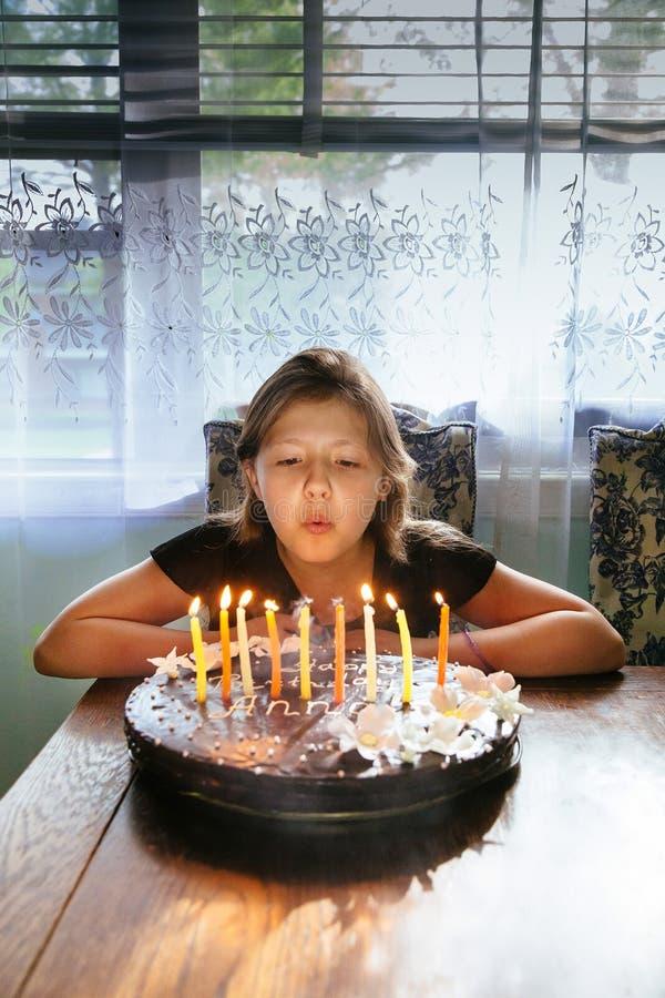 Ragazza graziosa che soffia le candele sul dolce fotografia stock