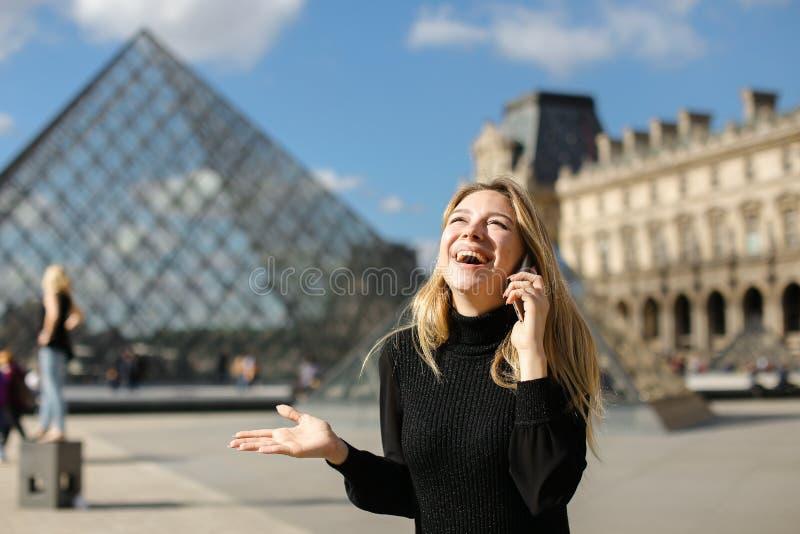 Ragazza graziosa che sta Louvre vicino e pyramind di vetro in vestito nero a Parigi, parlante dallo smartphone immagini stock libere da diritti