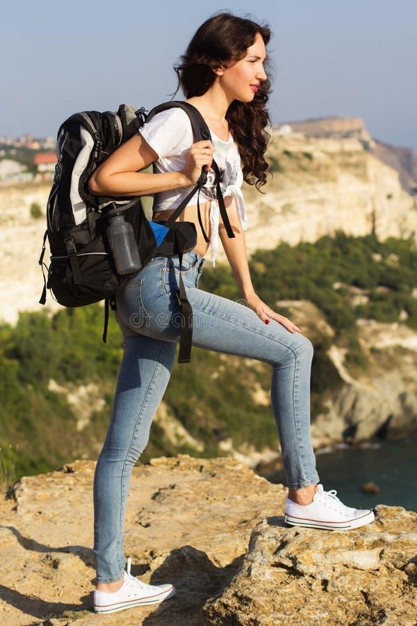 Download Ragazza Graziosa Che Sta Sulla Roccia Con Lo Zaino Fotografia Stock - Immagine di jeans, adulto: 56890682